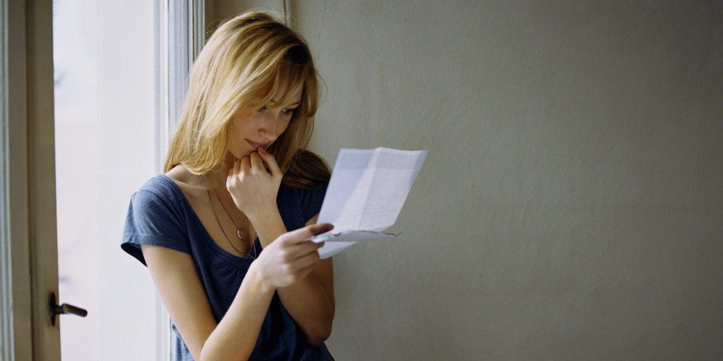 Young woman sitting on window ledge reading letter